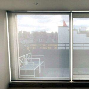 Transparent rullgardin monterad i fönster med lutning
